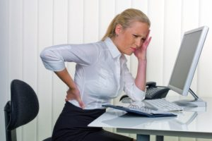 a woman with back pain from long sitting in the office. health and social welfare in the workplace.